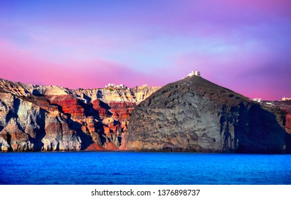 Santorini island, Cyclades, Aegean Sea, Southern Greece. Beautiful scenery, black volcanic rock with white castle at the top at the background of layered multicolor geological structure and sunset sky