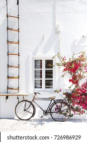 Santorini Island, Oia, Greece. Traditional white Greek architecture, part of the building with a window and a beautiful installation of a bicycle.