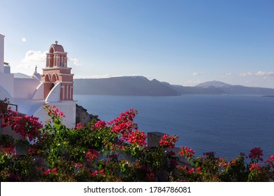 Santorini - Oia, a picturesque pink church tower built at the foot of a caldera, overgrown with pink oleander flowers. in the background the sea and islands in the middle of Caldera.