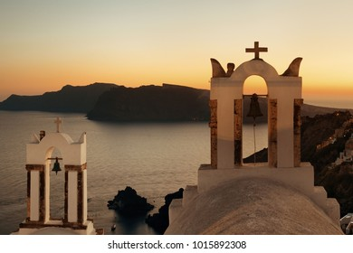 Santorini skyline at night with buildings and bell tower in Greece.
