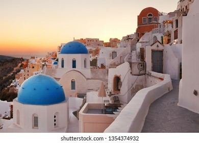 Santorini skyline sunset with blue church dome and buildings in Greece.