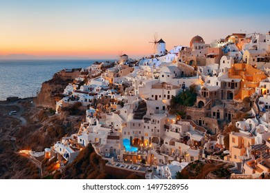 Santorini skyline sunset with windmill and buildings in Greece.