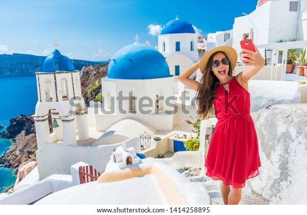 Santorini tourist girl on cruise holiday taking selfie photo with phone at famous three domes church, European tourism attraction in Greece. Asian woman on vacation.