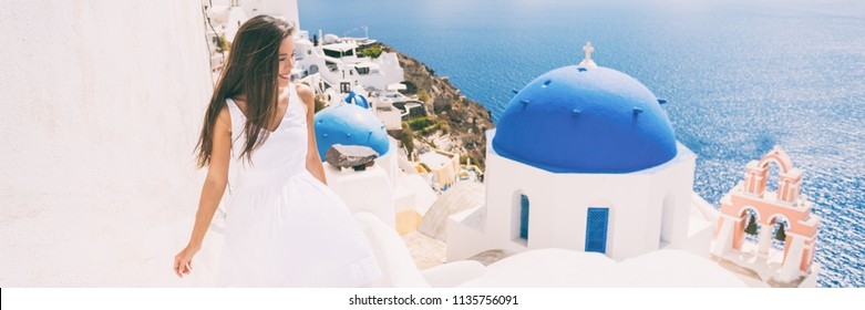 Santorini travel tourist woman on vacation in Oia walking on stairs visiting the famous white village with the mediterranean sea and blue domes. Europe summer destination panoramic banner.