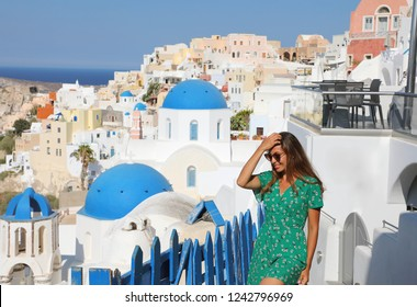 Santorini travel tourist woman on vacation in Oia walking on stairs. Girl in green dress visiting the famous white village with blue domes. Europe summer destination.