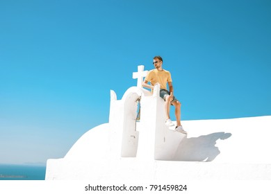 Santorini of a typical greek church overlooking the rock of skaros with the town of Oia and the volcano in the background, Young man sitting on a white greek church