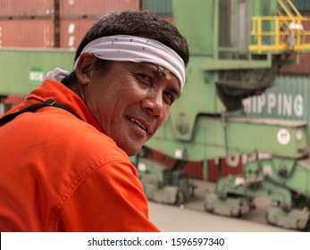 Santos, Brazil, February 02, 2013: A portrait of the asian seafarer with containers and gantry in the background.