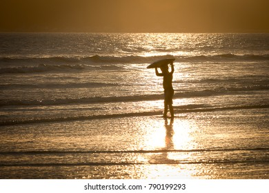 Santos, Brazil. January 05, 2018. A child going to play in the sea with his  morey boogie during sunset.