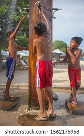 Sanur , Bali indonesia - 22 february 2013. Portrait of little boys taking shower on the beach, pretty child with pleasure refreshing in cold water