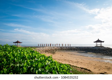 Sanur, Bali / Indonesia - December 24 2017: Beautiful view of a beach with happy people doing yoga in the morning