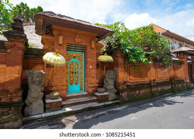 Sanur, Bali / Indonesia - December 24 2017: Wide view of a beautiful traditional Balinese house entrance with turquoise door and orange brick wall with statues and umbrellas on each sides