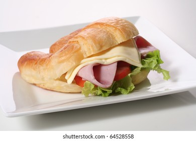 Sanwich Croissants with lettuce, cheese and tomatoes on a white background