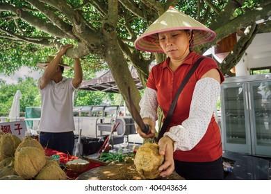 SANYA, CHINA - SEPTEMBER 13, 2015: Local woman cutting coconut.