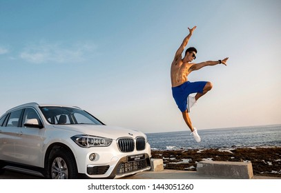 sanya, chsanyamay 20,2018: A bare-chested Asian muscle man jumps next to a BMW X1 SUV