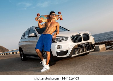 sanya, chsanyamay 20,2018: A bare-chested Asian muscle man is Leaning on a BMW X1 with a skateboard.