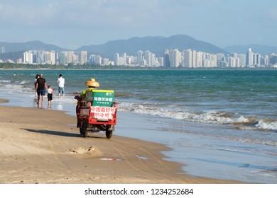 Sanya City, Hainan Province / China - January 26 2018: fruit seller on a moped in Sanya Bay