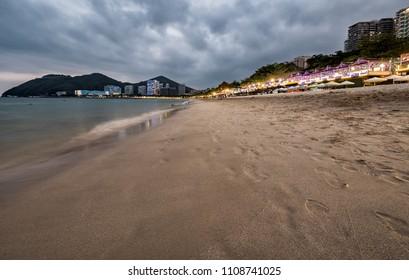 Sanya, Hainan beach at dusk with lights and dramatic clouds.