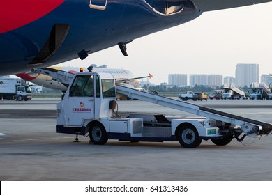 Sanya, Hainan, China April 25, 2017 - A car loading luggage on the runway of the airport Phoenix is preparing to be loaded into a Boeing 767-300