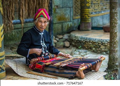 Sanya Li and Miao Village, Hainan, China - November 2017 - The indigenous inhabitants of the village are busy with their craft, weaving cloth.