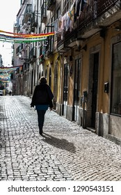 Sao Bento, Lisbon / Portugal - 12 28 2018: Young woman walking over the paved roads in the narrow old streets with typic colorful old houses