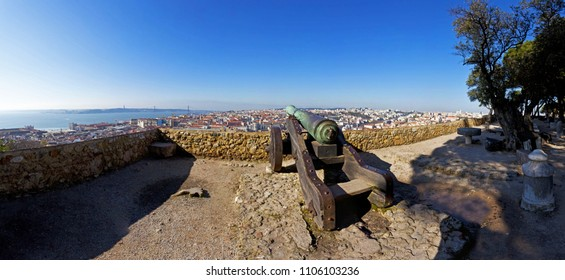 Sao Jorge (St. George) Castle in Lisbon, Portugal. Old Bronze cannon and a view of Lisbon's Baixa (downtown) District and river.