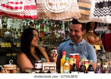 Sao Luis/Maranhao/Brazil - 09 08 2018: Girlfriend offering a pepper jelly for her boyfriend inside the craft fair