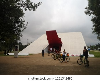 Sao Paulo, Brazil - 11/23/2014: Cyclists located at the entrance of the Ibirapuera Auditorium, in the Ibirapuera urban park in Sao Paulo, Brazil. Modernist architecture by Oscar Niemeyer.