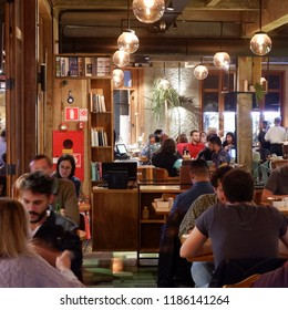 SAO PAULO, BRAZIL - 14 SEPTEMBER 2018: BUSY RESTAURANT HALL FILLED WITH PEOPLE SITTING AND DINING UNDER ROUND ELECTRIC BULBS LIGHTS