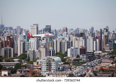 SAO PAULO, BRAZIL - AUG 10, 2017: Top view of buildings and airplane close to the Congonhas airport in the city of Sao Paulo, Brazil. Beautiful cityscape view with airplane merging the background.