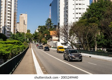 SAO PAULO - BRAZIL: AUG 12, 2020: Street view of Bernardino Tranchesi viaduct that runs between Bela Vista district buildings and over 9 de Julho avenue with traffic passing under sunny blue sky.
