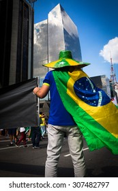 Sao Paulo, Brazil, August 16, 2015.  Brazilian activist, wearing the Brazilian flag and a typical hat,  holds a protest group against the government of PT on August 16, 2015 in Sao Paulo, Brazil