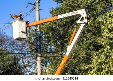 Sao Paulo, Brazil, August 26, 2015. Electrician repair system of electric wire, they wear safety working clothing, climb and work on electric pole of the local utility company