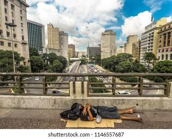 Sao Paulo, Brazil, February 22, 2018. Homeless man sleeping in floor of Cha Viaduct in downtown Sao Paulo