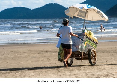 """Sao Paulo, Brazil, January 15, 2011. Seller walks with his cart for sale of green corn, with writing""""Green corn"""" in portuguese, on a beach in Peruibe, south coast of Sao Paulo state"""