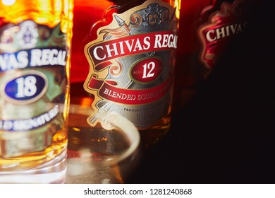SAO PAULO, BRAZIL - JANUARY, 2019: Two bottles of Chivas Regal 18yo and 12yo in a close-up view with backlight and shadows.