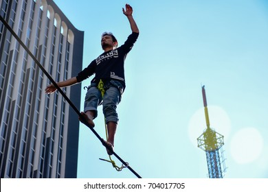 SAO PAULO, SAO PAULO - BRAZIL - JUL 30, 2017: Young man practicing slackline on top of the rope at the bottom buildings in Sao Paulo Avenida Paulista
