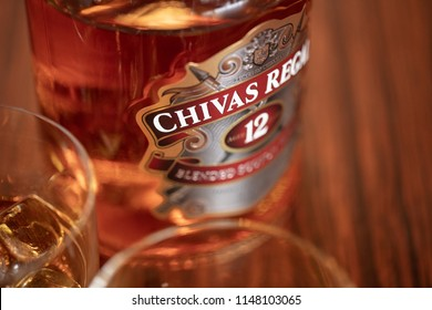SAO PAULO, BRAZIL - JULY 20, 2018: A bottle of Chivas Regal 12yo with two glasses in close-up with shallow depth of the field and at a wood background.