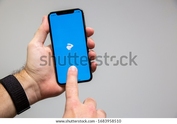 Sao Paulo, Brazil; March 25, 2020: Man holding a Smartphone with Loggi logo on it. Loggi is a Brazilian company in the segment of delivery, Brasilian Fintech.