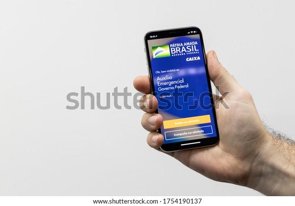 Sao Paulo, Brazil; May 02, 2020: Caixa bank application, to provide emergency aid in Brazil (Coronavoucher), due to the covid-19 pandemic. Translation: Brazilian Emergency Aid App (App CAIXA)