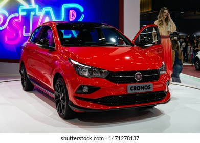 SAO PAULO, BRAZIL - NOVEMBER 15, 2018: A red Fiat Cronos subcompact sedan car with a trade show model standing beside it displayed inside Fiat pavilion at 2018 Sao Paulo International Motor Show.