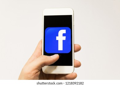 Sao Paulo, Brazil - November 2018: Male hand holding cell phone with Facebook logo. Smartphone App.