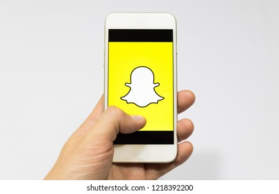 Sao Paulo, Brazil - November 2018: Male hand holding cell phone with Snapchat logo. Smartphone App.