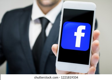 Sao Paulo, Brazil - November 2018: Business man wearing suit and tie holding smartphone with Facebook company logo.
