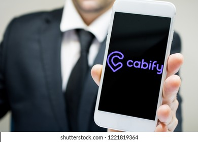 Sao Paulo, Brazil - November 2018: Business man wearing suit and tie holding smartphone with Cabify company logo.