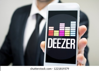 Sao Paulo, Brazil - November 2018: Business man wearing suit and tie holding smartphone with Deezer company logo.