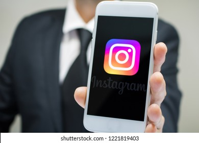 Sao Paulo, Brazil - November 2018: Business man wearing suit and tie holding smartphone with Instagram company logo.