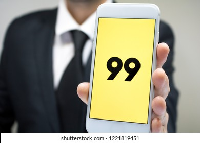 Sao Paulo, Brazil - November 2018: Business man wearing suit and tie holding smartphone with 99 Taxi company logo.