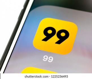 Sao Paulo, Brazil - November 2018: Cell phone screen with 99 taxi logo. Smartphone App.