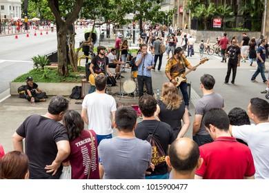 Sao Paulo, Brazil - November, 26 2017.  Sunday at Paulista Avenue (Avenida Paulista), business and financial street downtown. Pedestrians watch street performers on the sidewalk.