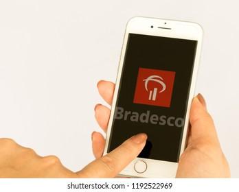Sao Paulo, Brazil - October 2018: Female hand holding Iphone cell phone with Bradesco Bank logo. Smartphone App. Brazilian bank.
